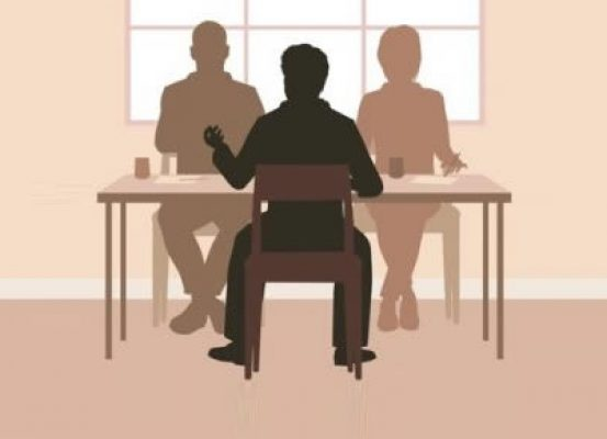 Silhouettes of people sitting at a table holding a discussion
