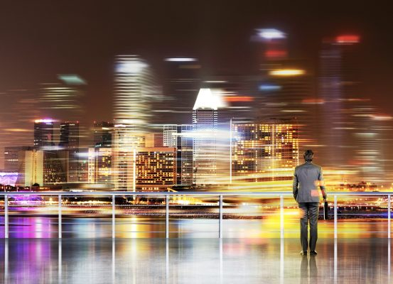 Businessman with hands in pockets, New York view at night. Enbankment. Double exposure. Concept of work.