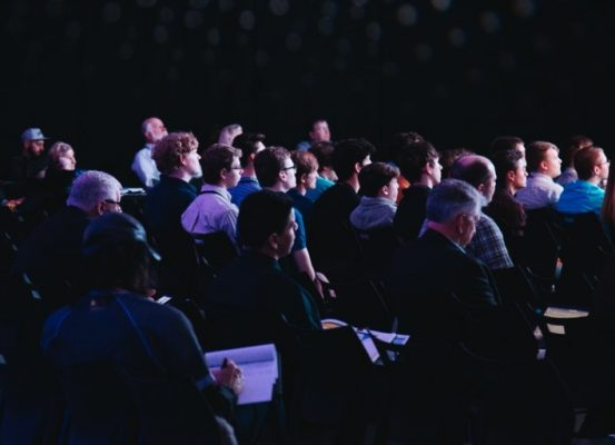 Audience watching a keynote speaker during a conference