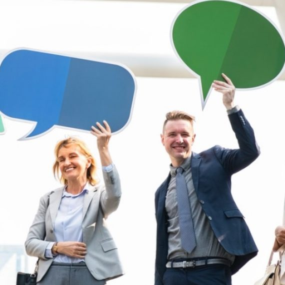 Four business people holding cut-out communication bubbles above their heads.