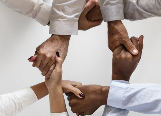A group of four people interlocking hands in a circle pattern