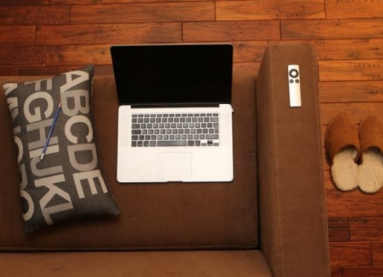 A picture of a laptop sitting on a couch meant to depict working from home