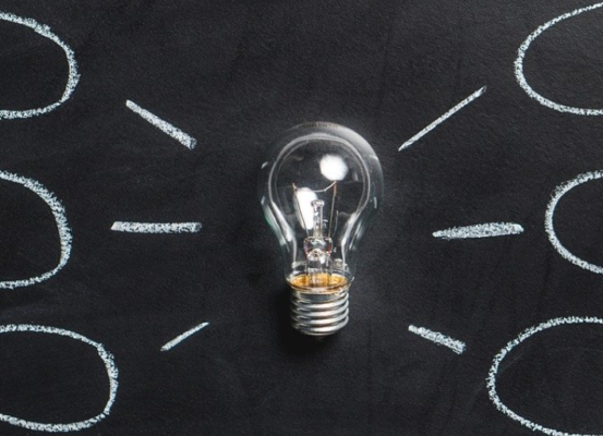 Light bulb in front of a chalkboard with six thought bubbles coming off of it