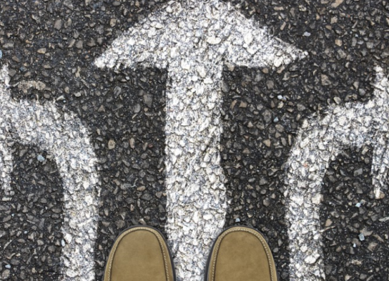 A pair of shoes overlooking arrows painted on the ground facing left, right, and forward