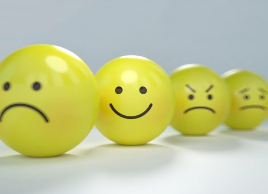 Four balls. three with sad faces, one with a smile