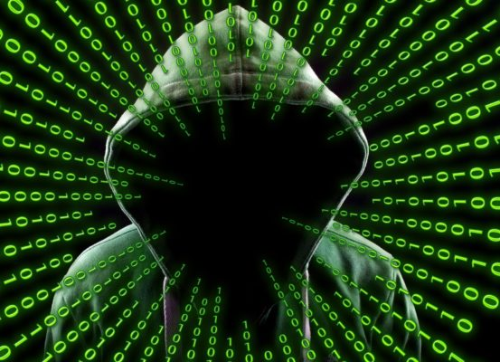 A hooded cyber criminal surrounded by binary code