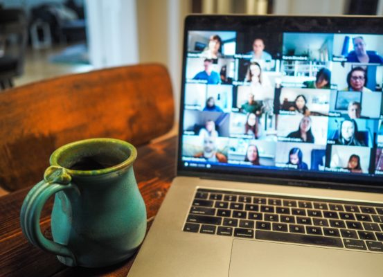 A coffee mug sat next to an open laptop which is displaying a virtual conference