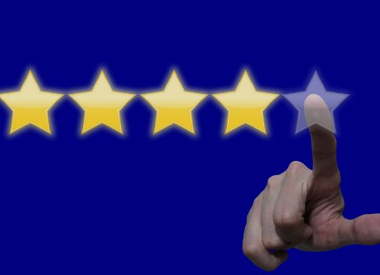 A hand reaching out to press a star in order to leave a 5 star review