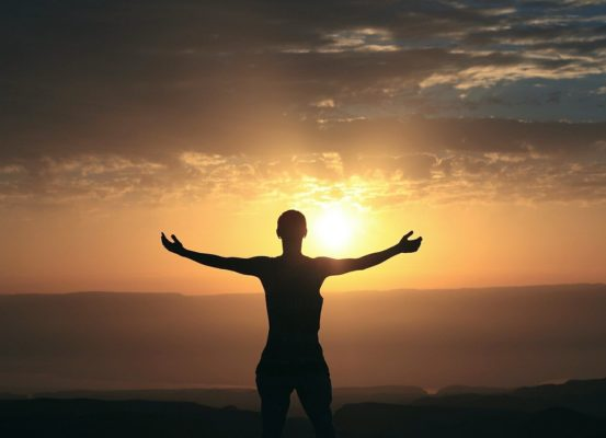 A woman, with arms spread, welcoming a sunrise. Meant to depict being thankful.