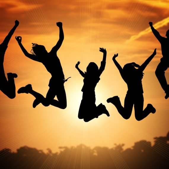 Silhouettes of 5 people jumping for joy celebrating success
