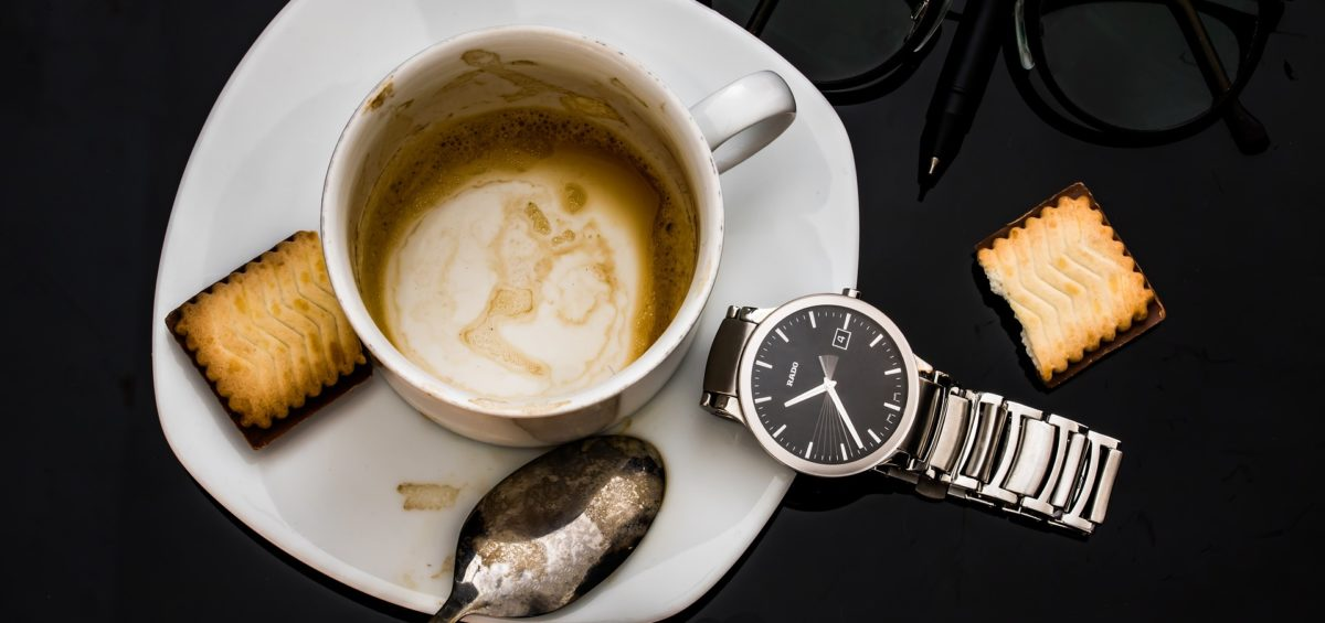 An empty coffee cup on a table along with a watch and glasses